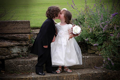 Page boy kissing flower girl